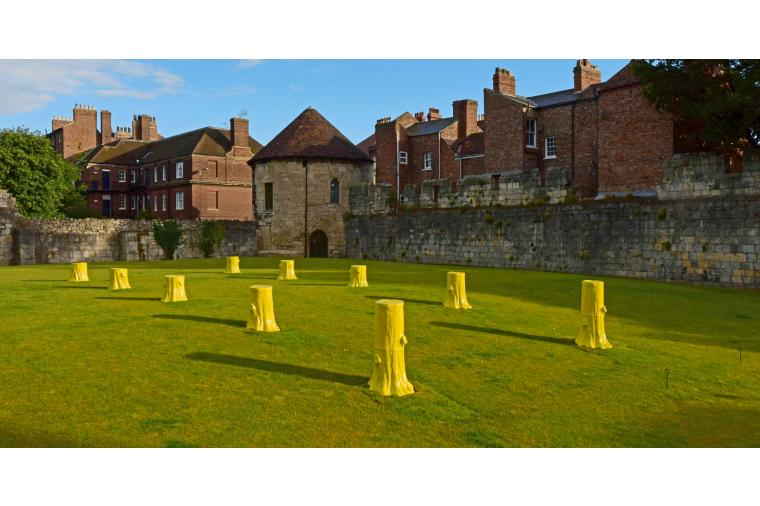 1) Foundation Myths comprises ten, life-sized, ceramic tree stumps arranged geometrically in two rows