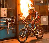 Dougie Lampkin rides past furnaces at Wallwork Heat Treatment