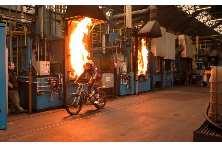 1a) 12 times Trials World Champion, Dougie Lampkin, rides past flaming furnaces at Wallwork Heat Treatment
